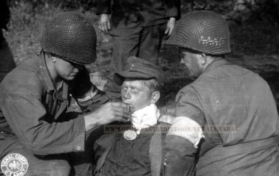 9th Division men aid German wounded soldier