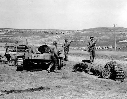 US Infantry men and a destroyed German Armored Fighting Vehicle
