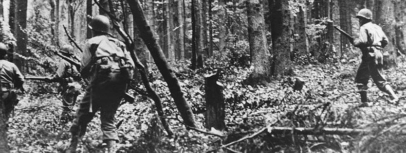 US Infantry men moving cautiously through the Hurtgen Forest
