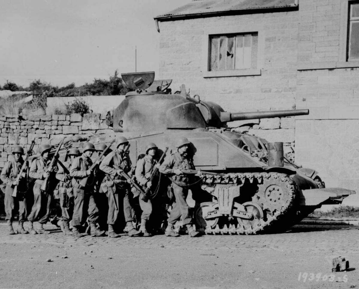 Infantry men advance under the cover of a M4 Sherman tank in Sprimont, Belgium, 9th September 1944.