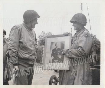 Major Frank Gunn of 1st Battalion, 39th Infantry Regiment, shows a picture of a German officer believed to have been the head of the Cherbourg Region to Major General Manton S. Eddy. Both men are smiling at the picture, which was found in the captured German headquarters in Cherbourg. Picture taken on July 1st, 1944.
