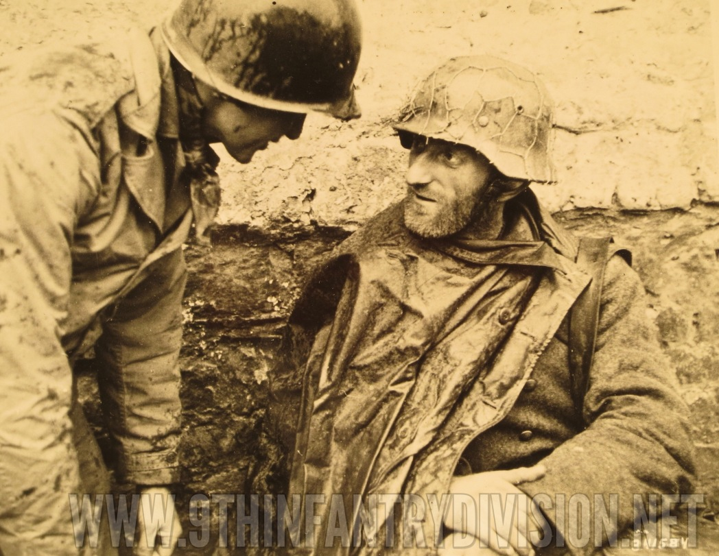 An American soldier talks to one of the German prisoners.