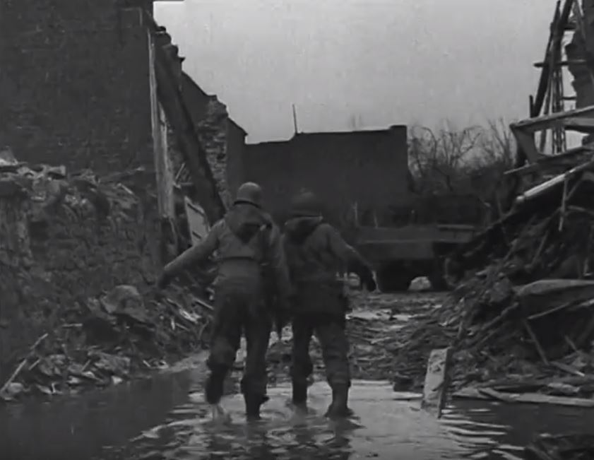 2 American GIs walk towards the truck to pick up the prisoners.